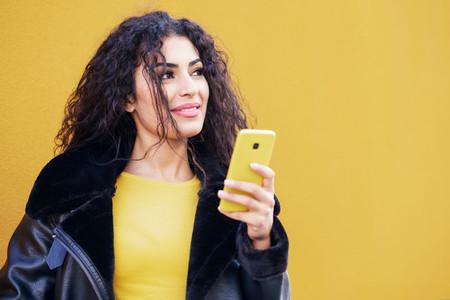 Arab woman walking in the street using her smartphone