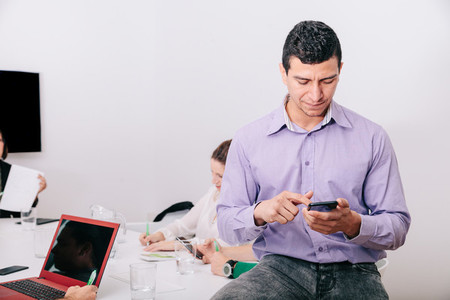 A businessman using his cellphone sitting at the office table