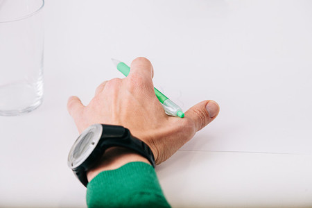 Closeup of hand over white table with a pen