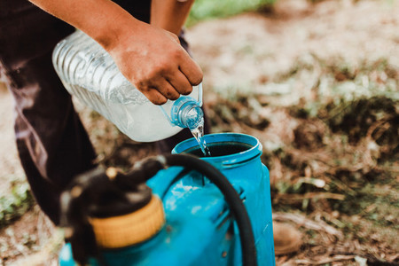 Young farmer preparing organic fertilizer with manual pump tank