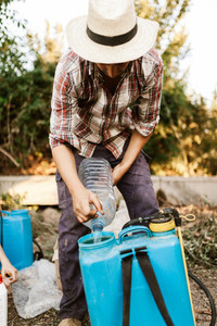 Young farmer preparing organic fertilizer with manual pump tank
