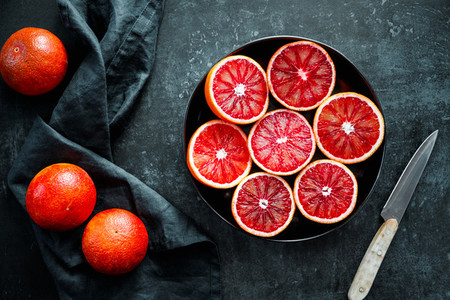 Cutted blood oranges in a plate on a black background
