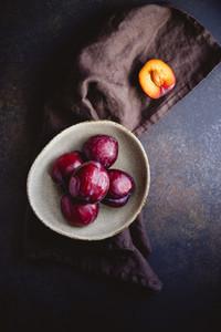 High angle view of fresh purple plum on a dark linen Food photography still life