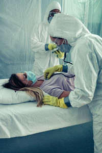 Doctors with bacteriological protection suits attending a patien