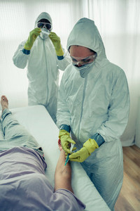 Doctors injecting a vaccine to a patient