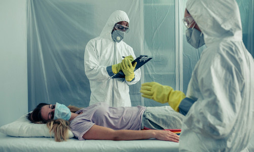 Doctors with bacteriological protection suits examining a patien