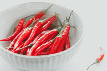 Chili peppers in a white ceramic bowl on a table Close up view