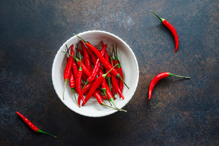 Chili peppers in a white ceramic bowl on a table Top view