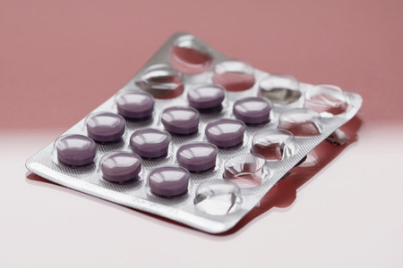 Close up of purple pills in a pack on a pink background