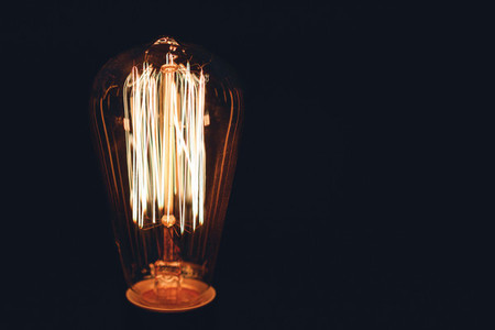 Close up of glowing retro light bulb on a black background Copy space