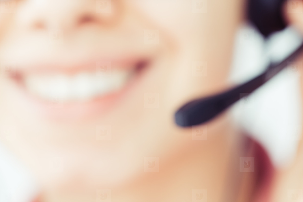 Smiling girl in the headset is working in the customer support center  Blurred image