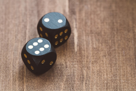 Close up of black dice on a wooden table