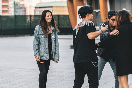 ITALY MILAN   23 SEPTEMBER 2017 Young Asian guys ask the girl to take a picture on Piazza Gae Aulenti Milan
