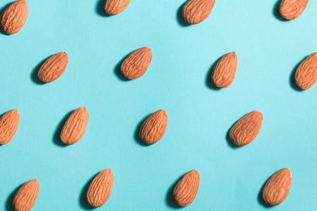 Symmetrical pattern of almonds on blue Flat lay