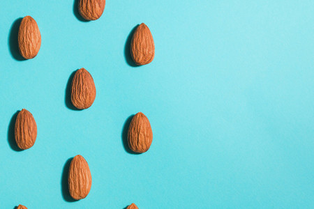 Symmetrical pattern of almonds on blue  Flat lay