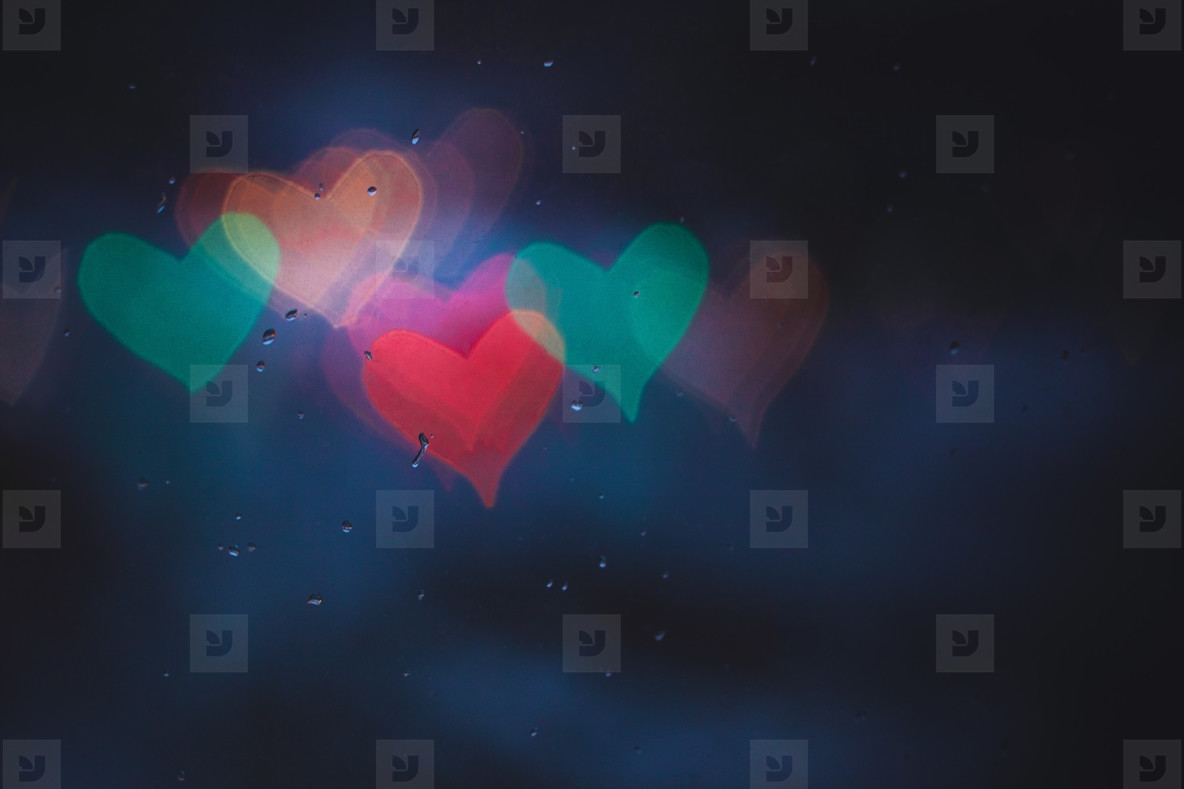 Colored blurred lights in the shape of heart through window with rain drops at night  Copy space
