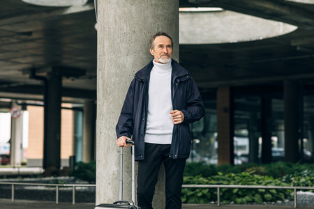 Stylish senior tourist standing