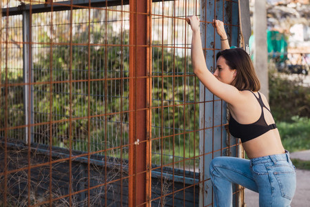 Young woman look inside through a fence