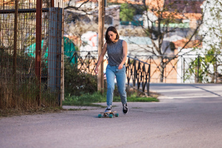 Young skater woman riding on her longboard in the village