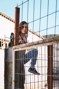 Young woman skater trying to climb over the fence
