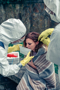 Doctors putting protective mask on woman infected with a virus