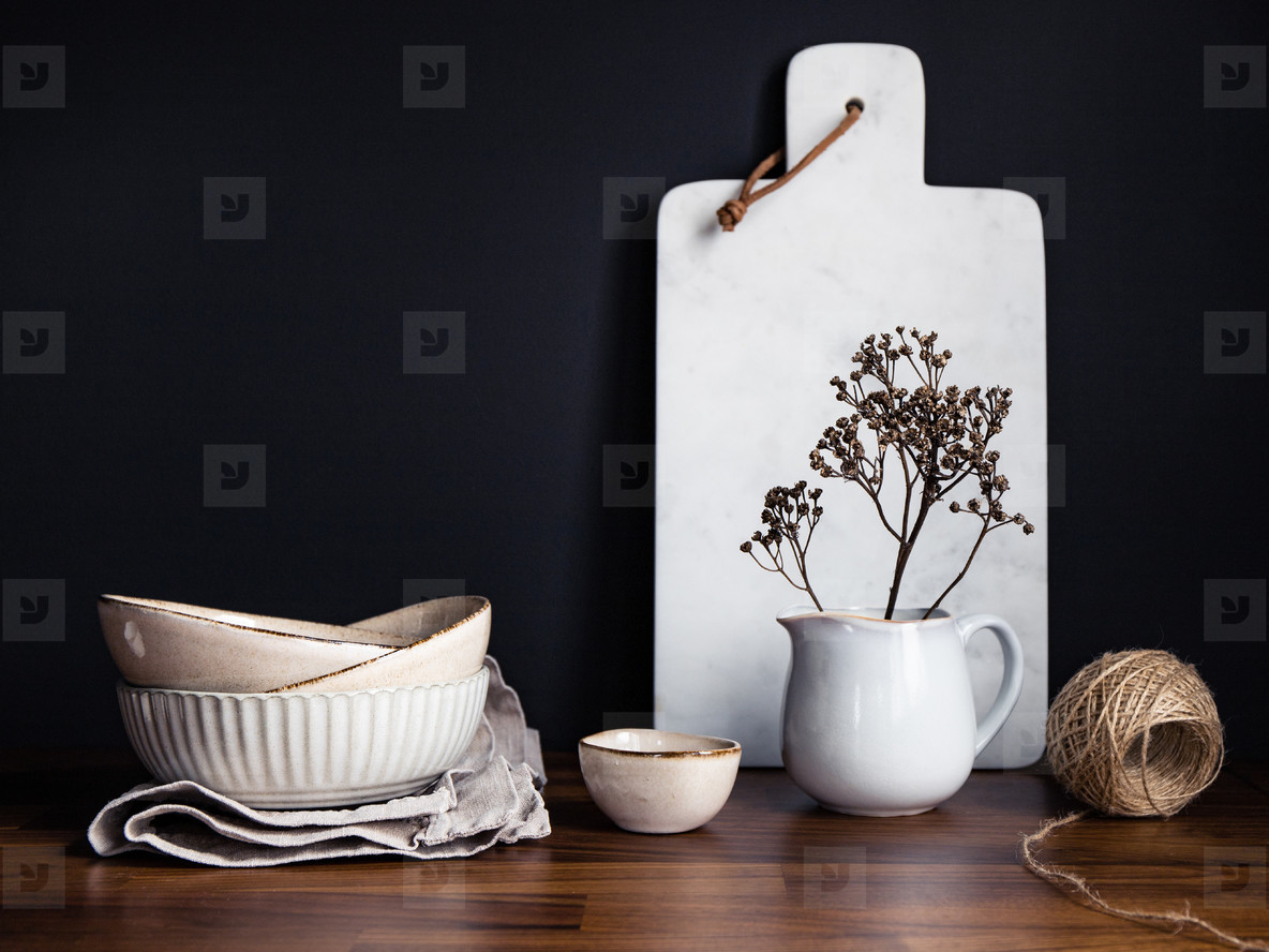 Set of kitchen ceramic tableware and white marble cutting board on a wooden table  Eco style home still life