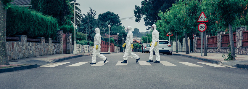 People in bacteriological protection suits walking down an empty