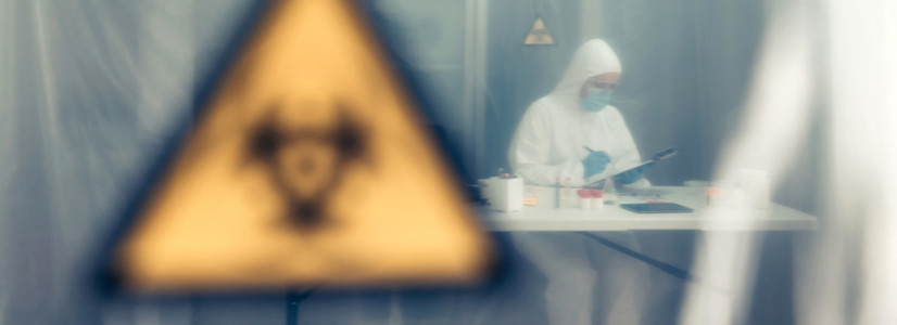 Scientist investigating in the laboratory behind a protective cu