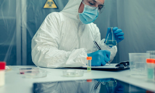 Scientist with protection suit investigating in the laboratory