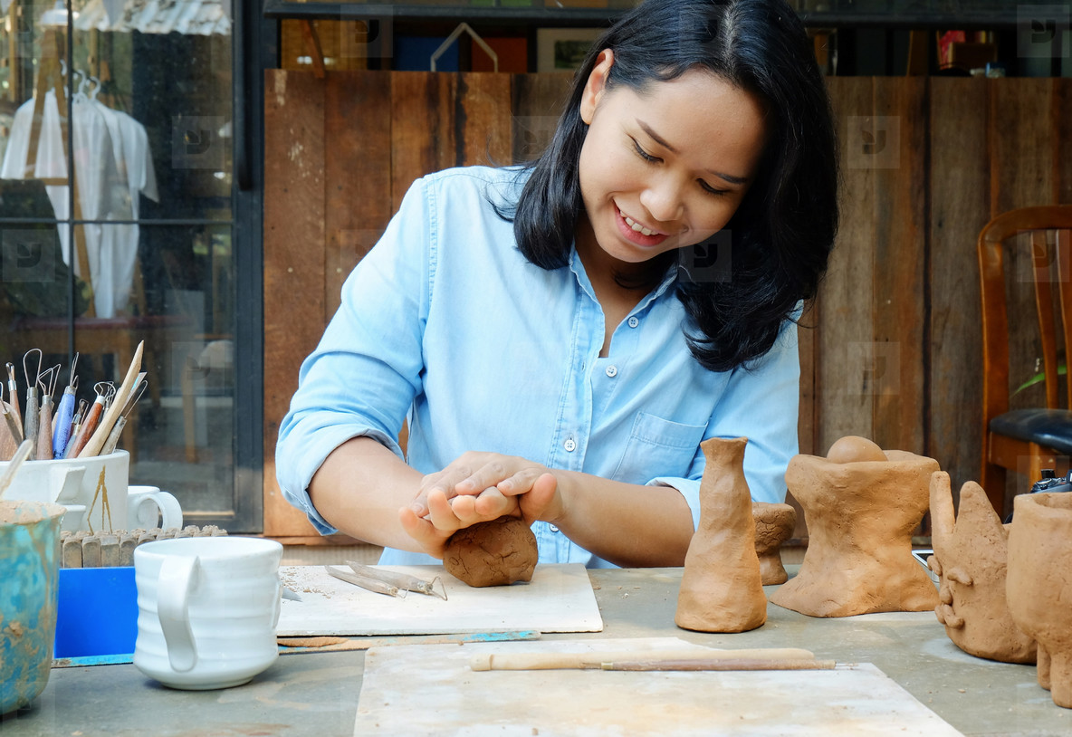Asian adult woman molding handmade cray in studio  hobby and lif