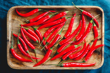 A lot of chili peppers on a wooden tray  Top view