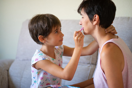 Mother and her little daughter doing make up for each other
