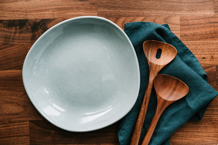 Empty ceramic plate for salad with wooden kutchen tools on a wooden table Eco style home still life top view