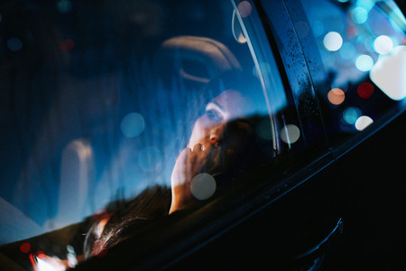 Young woman inside a car looking away through the window