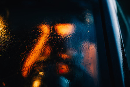 Person unfocused through the window car with drops