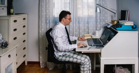 Man teleworking wearing shirt tie and pajama pants