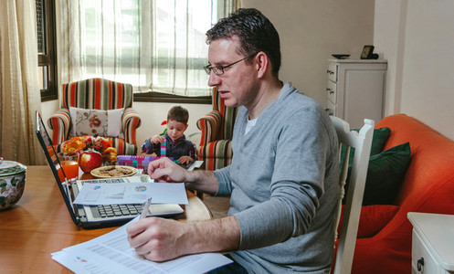 Father working at home while her son plays