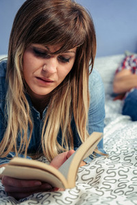 Young woman reading a book lying on the bed