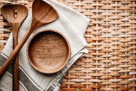 Cooking eco style background Wooden kitchen tools and bowl on a rattan