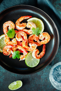 Fried tiger shrimp with lime  lemon and spices on a black plate  Healthy dinner or lunch concept