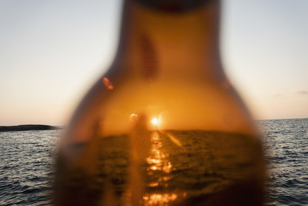 Sunset over ocean through brown glass beer bottle