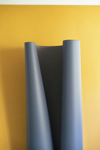 Gray sheet unrolling on yellow background