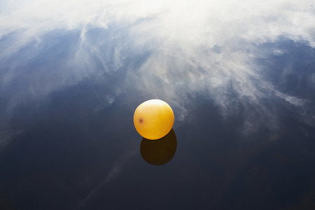 Yellow balloon floating on placid water reflecting clouds
