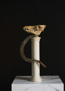 Animal skull and scythe on pedestal