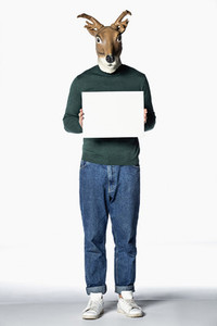 Man in reindeer mask holding blank sign