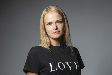 Portrait confident young woman in love t shirt on gray background