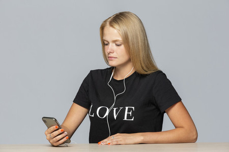 Young woman in love t shirt listening to music