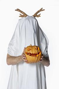 Portrait playful man in sheet costume holding jack o lantern