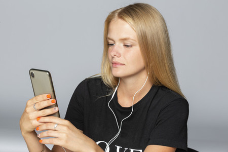 Young woman listening to music with smart phone and headphones