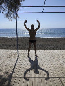 Silhouette and shadow of man stretching on sunny beach deck